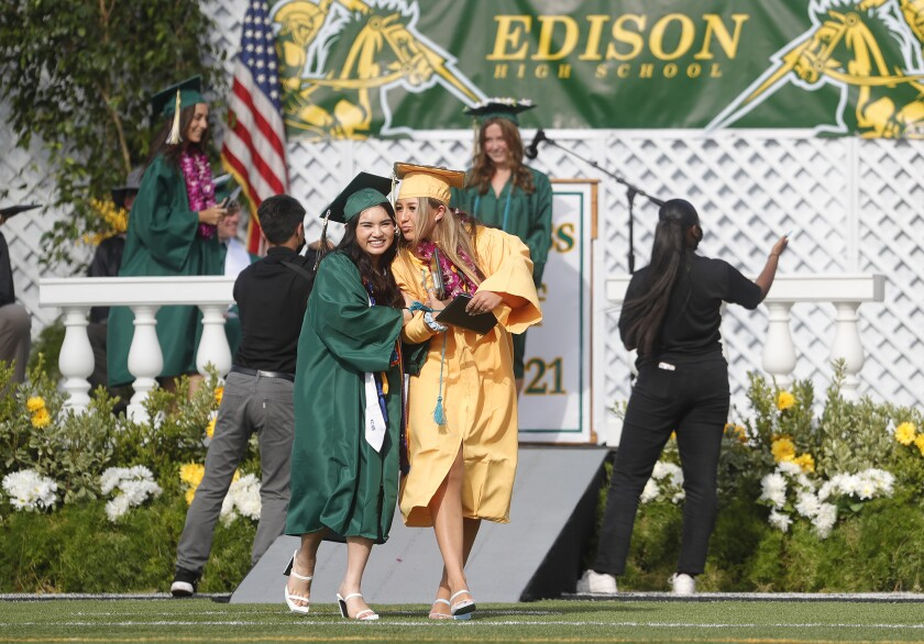 Two friends walk together after receiving their diplomas at the 2021 Edison High graduation ceremony.