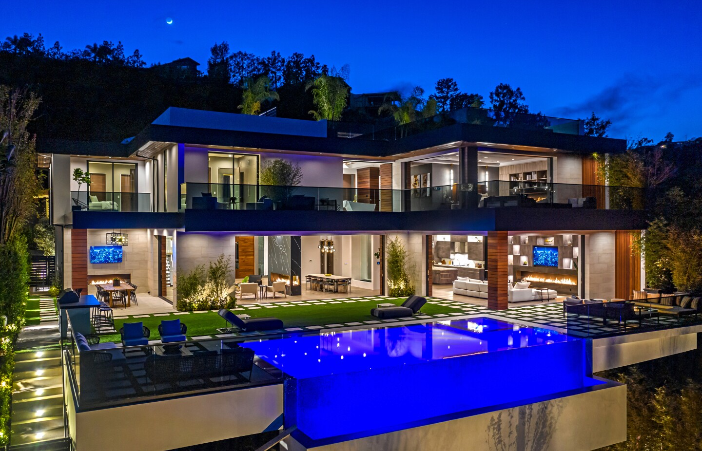 Accent lighting and modern fixtures enhance the visual allure of this newly built home in Brentwood. Listed for $12.899 million, the six-bedroom, nine-bathroom residence was built by Huntington Estate Properties and sits on about a third of an acre with an infinity-edge swimming pool. High ceilings, marble slabs and a floating glass-and-steel staircase are among features of the 9,300-square-foot showplace. An illuminated waterfall feature and a two-way fireplace bookend the dining room. Other amenities include a movie theater, a wine room and a gym. Atop the house, a rooftop deck takes in tree-top and canyon views.