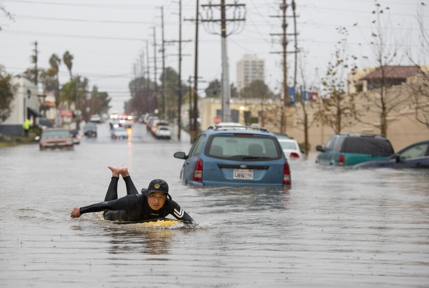 Joe Suzuki paddles past submerged cars on Pomona Avenue near 17th Street in Costa Mesa on Thursday afternoon.