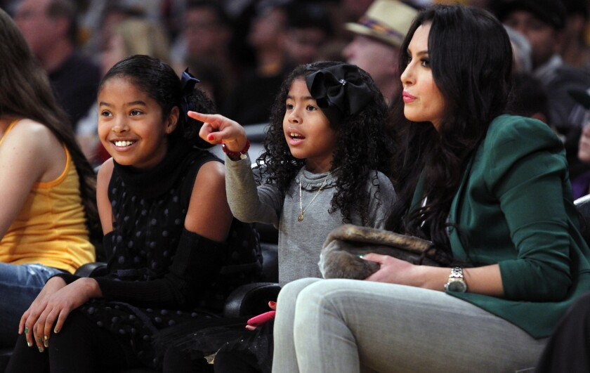 Vanessa Bryant, right, sits with her daughters (from left) Natalia and Gianna during a game between the Lakers and New York Knicks at Staples Center on Christmas Day in 2012.