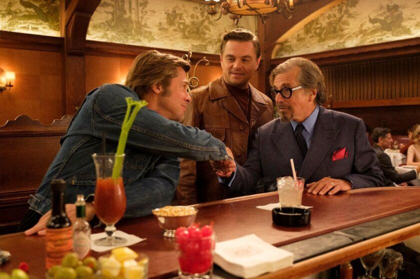 """Brad Pitt, left, and Al Pacino shake hands seated at the bar at Musso & Frank's in """"Once Upon a Time ... in Hollywood."""" Leonardo DiCaprio stands between them."""
