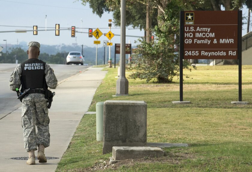 A military police officer patrols the perimeter of the US Army IMCOM HQ building prior to the Article 32 preliminary hearing to determine if Army Sgt. Bowe Bergdahl will be court-martialed, Thursday, Sept. 17, 2015, at Fort Sam Houston in San Antonio. Bergdahl, who left his post in Afghanistan and was held by the Taliban for five years, is charged with desertion and misbehavior before the enemy. (AP Photo/Darren Abate)