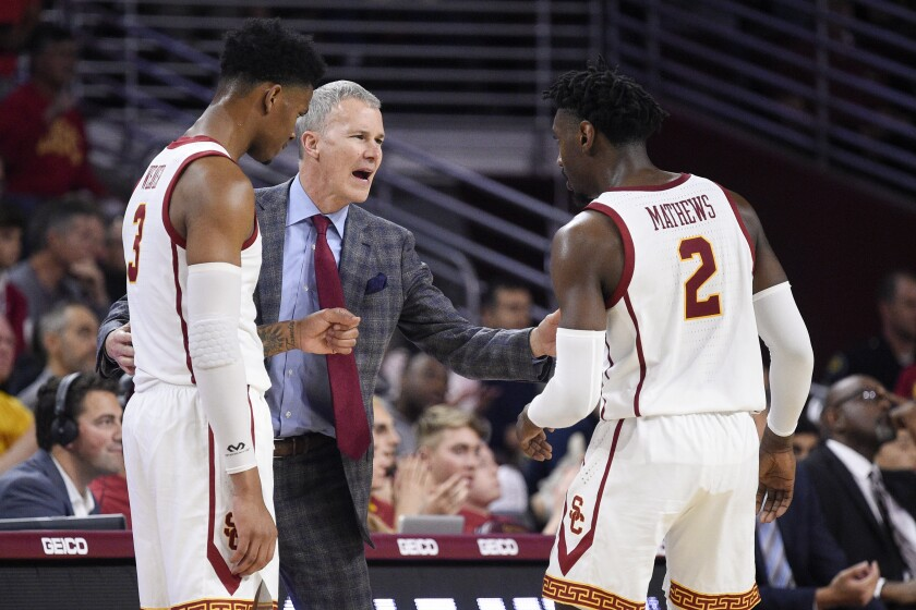 USC coach Andy Enfield talks with Jonah Mathews and Elijah Weaver during a game against Stanford in January.
