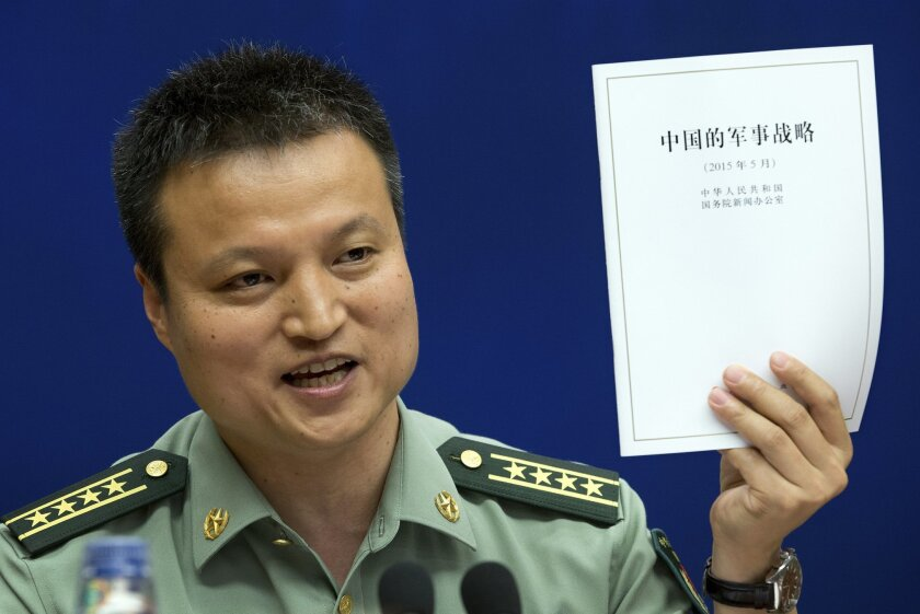China's Defense Ministry spokesman Yang Yujun holds up a report on China's Military Strategy during a press conference at the State Council Information Office in Beijing, China, Tuesday, May 26, 2015. China's military on Tuesday compared its controversial island-building in the South China Sea to ordinary construction such as road-building going on elsewhere in the country, trying to deflect criticism over an issue seen as inflaming tensions in the region. (AP Photo/Andy Wong)