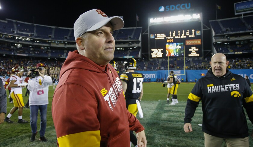 USC coach Clay Helton walks on the field after the Trojans' loss to Iowa in the Holiday Bowl.