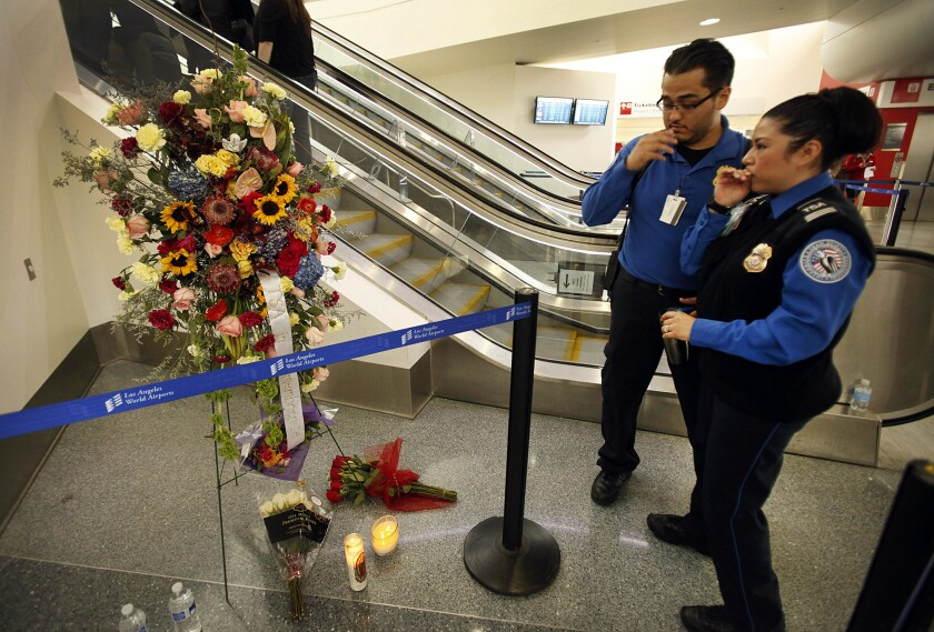 Transportation Security Administration agents leave flowers and say a prayer at the site where TSA Officer Gerardo Hernandez was shot to death inside Terminal 3 at LAX.