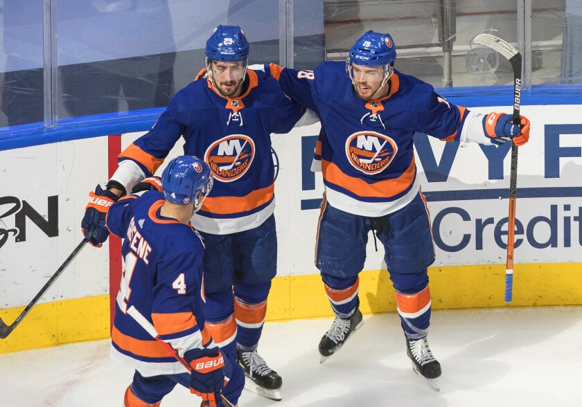 New York Islanders' Andy Greene (4), Brock Nelson (29) and Anthony Beauvillier (18) celebrate a goal on the Tampa Bay Lightning during the second period of Game 3 of the NHL hockey Eastern Conference final, Friday, Sept. 11, 2020, in Edmonton, Alberta. (Jason Franson/The Canadian Press via AP)