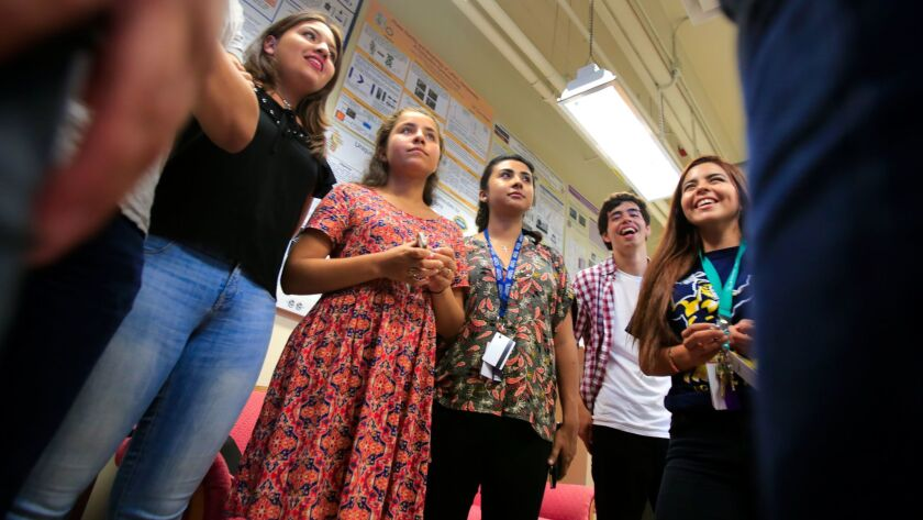 High school students from Baja California and San Diego pictured in August 2016 discuss the science projects completed during a seven-week program on the UCSD campus that allowed them to carry out hand-on research under faculty supervision.