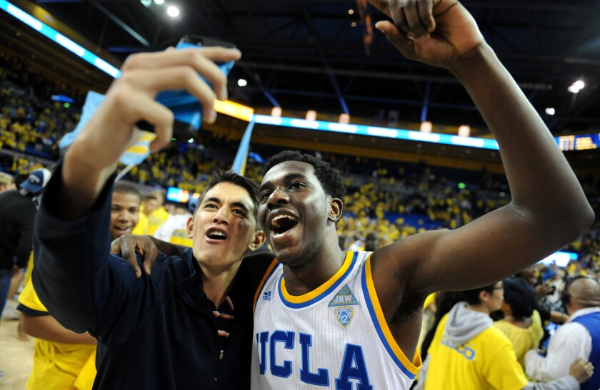 UCLA's Prince Ali takes a selfie with a fan after defeating Kentucky at Pauley Pavillion.
