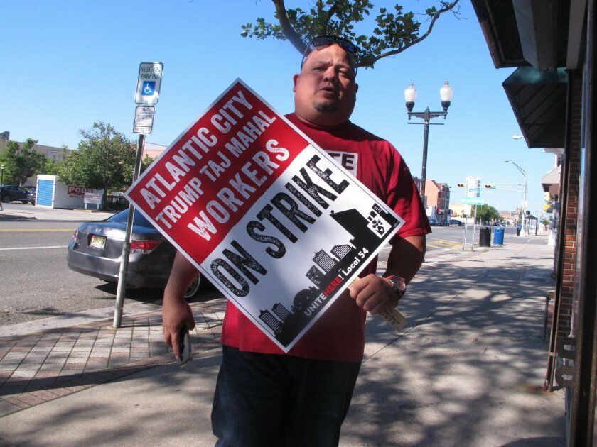 A casino worker carries a picket sign on Thursday June 30, 2016 in Atlantic City N.J. as contract talks between his union, Local 54 of Unite-HERE and the Trump Taj Mahal were underway to try to prevent a threatened Friday strike. The union earlier in the day had reached agreement with the four othe