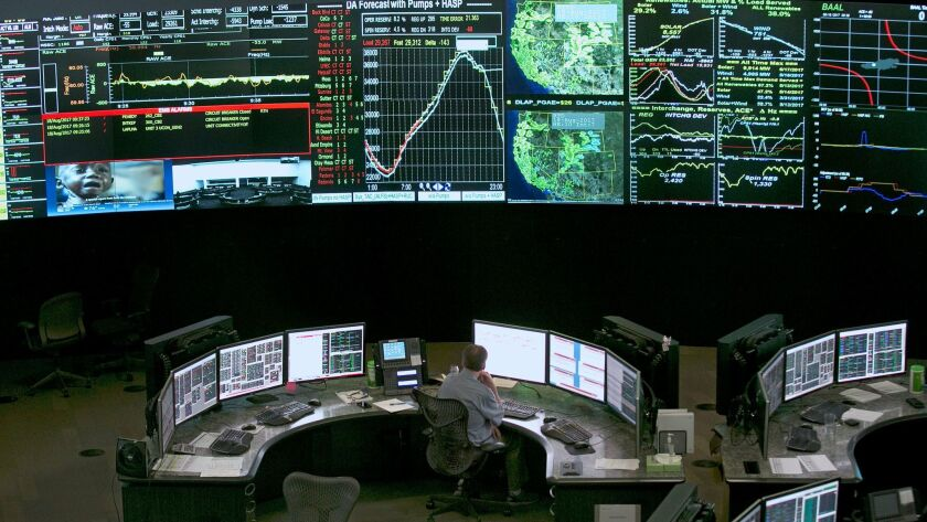 Electrical power flow and conditions are monitored at the California Independent System Operator grid control center in Folsom on Aug. 18.