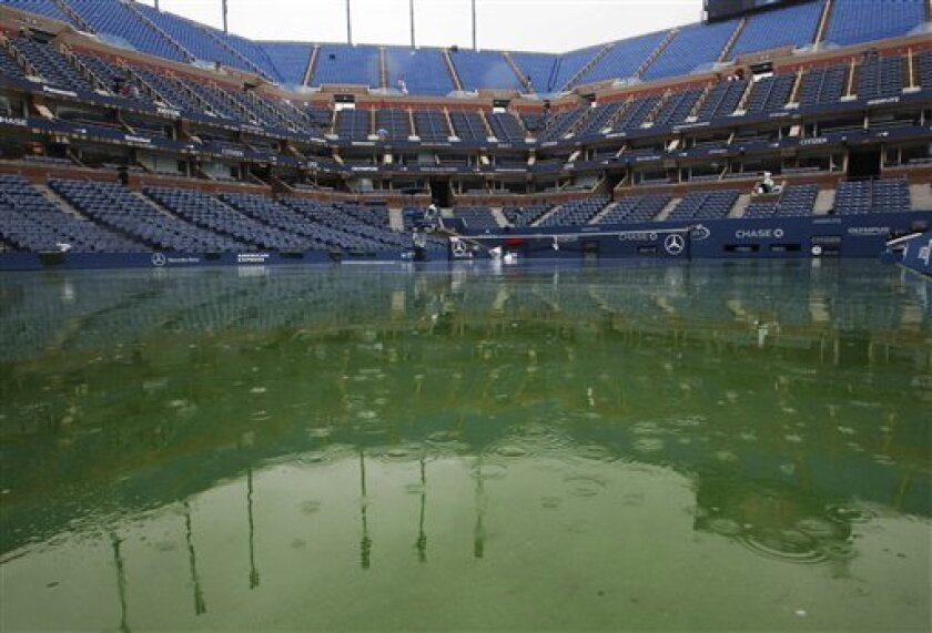 Water gathers on the court at Arthur Ashe Stadium during the U.S. Open tennis tournament in New York, Tuesday, Sept. 6, 2011. The start of play at the U.S. Open is being delayed because of rain. (AP Photo/Mel Evans)