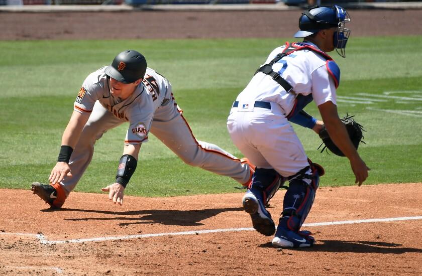 The Giants' Tyler Heineman scores around Dodgers catcher Austin Barnes in the fourth inning July 25, 2020.