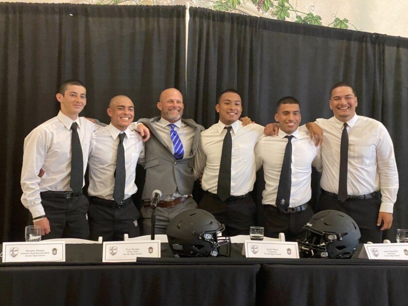 Servite players surround coach Troy Thomas for a photo at Trinity League media day.