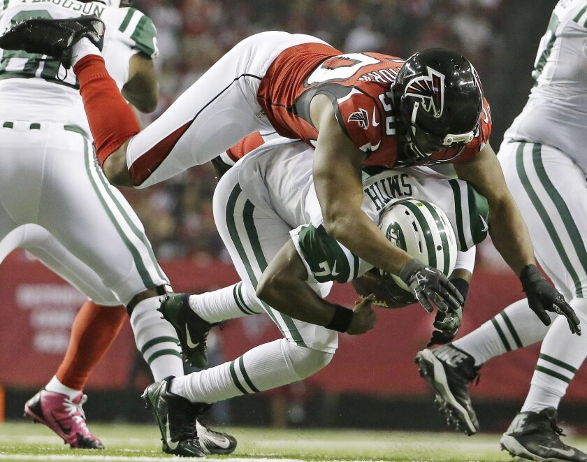 FILE - In this Oct. 7, 2013, file photo, New York Jets quarterback Geno Smith (7) is sacked by Atlanta Falcons defensive end Osi Umenyiora (50) during the second half of an NFL football game in Atlanta. Umenyiora still plays video games online with former Giants teammate Victor Cruz. On Sunday, Oct. 5, 2014, they'll go against each other for real for the first time. (AP Photo/David Goldman, File)