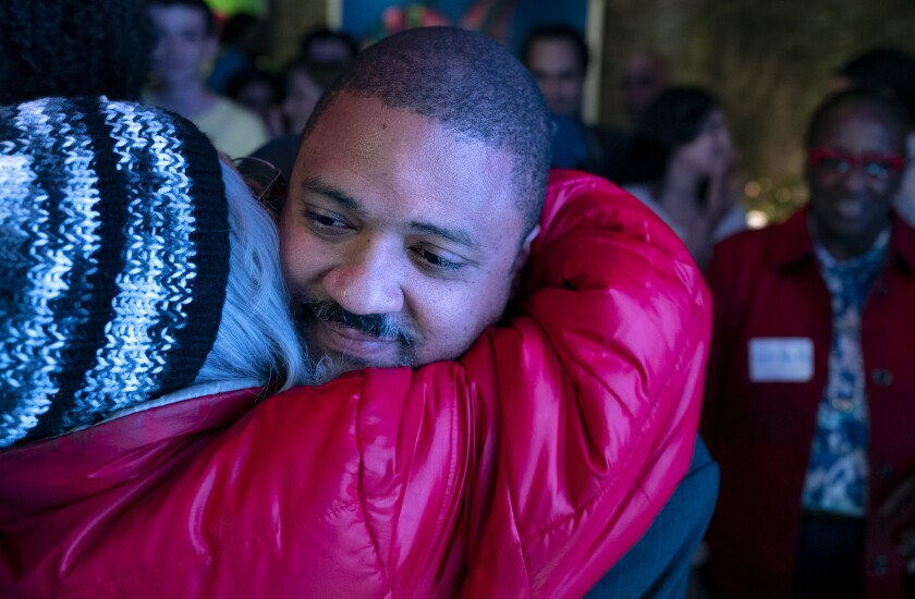 Alvin Bragg, a former top deputy to New York's attorney general, is embraced after speaking to supporters in New York, late Tuesday, June 22, 2021. (AP Photo/Craig Ruttle)