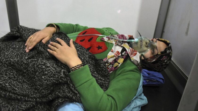 In this photo released by the Syrian official news agency SANA, shows a woman receiving oxygen throu