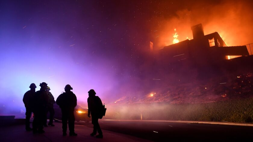 Firefighters monitor a house fully engulfed on Mountain Crest Circle in Thousand Oaks early Nov. 9. The Woolsey fire destroyed more than 1,600 structures in L.A. and Ventura counties, many of which were homes.