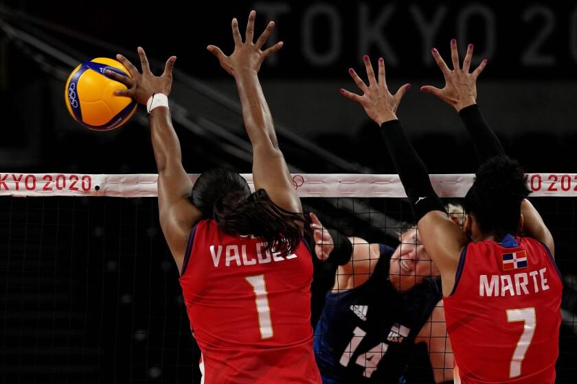 La estadounidense Michelle Bartsch-Hackley (centro) ejecuta un spike durante el duelo de cuartos de final del vóleibol femenino contra la República Dominicana, el miércoles 4 de agosto de 2021. (AP Foto/Frank Augstein)