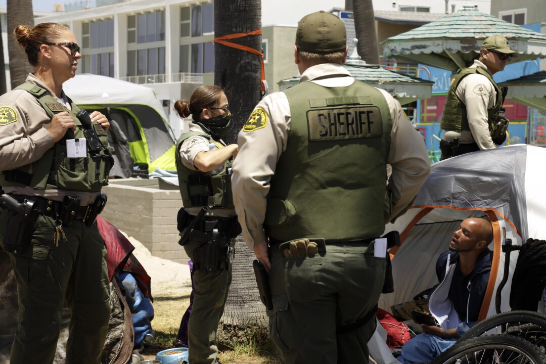 Sheriff's deputies talk to a man in a tent.