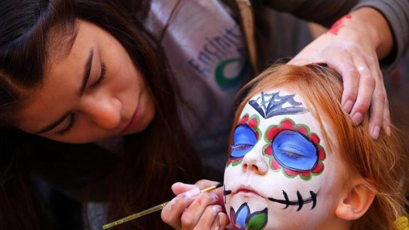 Georgia Baird, 6, gets her face painted for the Day of the Dead celebration at the Encinitas Library Saturday by Sophia Hernandez, 17. (Bill Wechter)