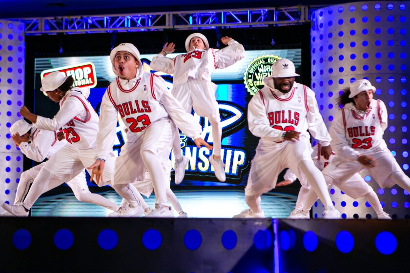 A dance crew in Chicago Bulls jerseys over white shirts and pants.
