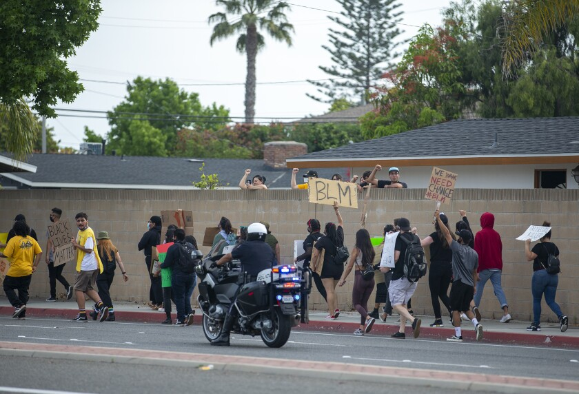 Protesters walk along Fairview Rd. as a Costa Mesa police officer patrols the street on Tuesday.