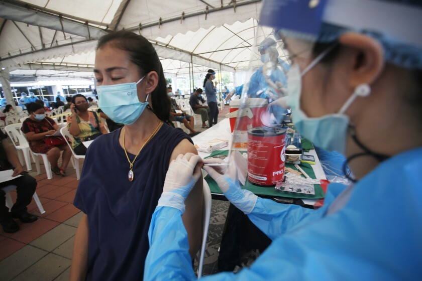 FILE - In this Tuesday, May 4, 2021, file photo, a health worker administers a dose of the Sinovac COVID-19 vaccine to residents of the Klong Toey area, a neighborhood currently having a spike in coronavirus cases, in Bangkok, Thailand. Thailand sought Thursday, may 6, 2021, to assure its foreign residents that they can get COVID-19 vaccinations, countering comments by some officials suggesting they would be at the end of the line for inoculations. (AP Photo/Anuthep Cheysakron)
