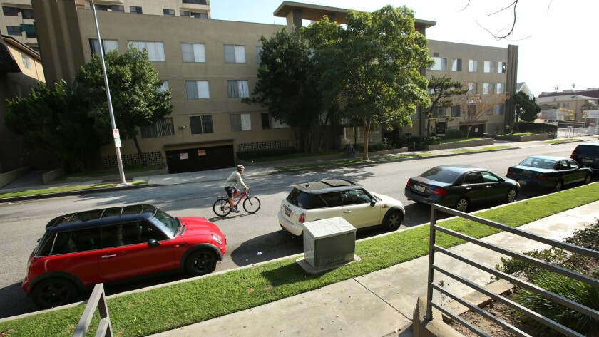 A bicyclist peddles by a row of parked cars on Kingsley Drive in Koreatown.
