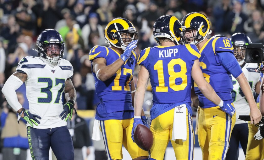 Rams quarterback Jared Goff (16) celebrates after throwing a touchdown pass to receiver Cooper Kupp (18) against the Seattle Seahawks at the Coliseum on Dec. 8.