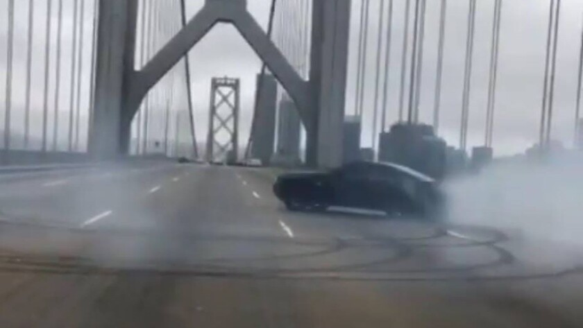 "A black Ford Mustang does ""doughnuts"" on the Bay Bridge in San Francisco on Sunday afternoon."
