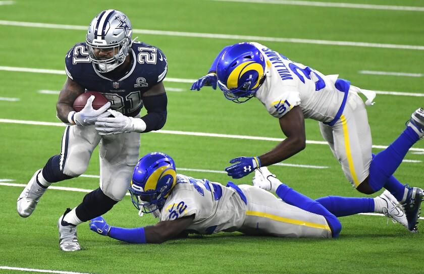Cowboys running back Ezekiel Elliott eludes Rams defenders Jordan Fuller (32) and Darious Williams on Sept. 14, 2020.