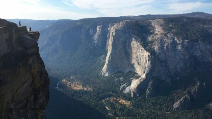 A wedding couple is seen being photographed at Taft Point in Yosemite National Park.