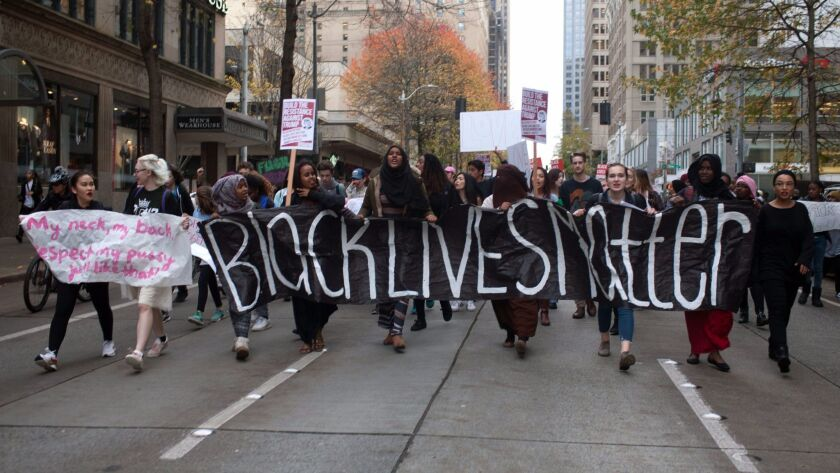 """Protesters carry a """"Black Lives Matter"""" banner as they march through downtown Seattle in November."""