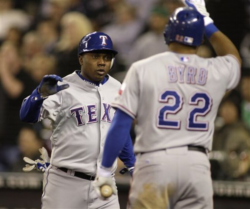 Texas Rangers' Esteban German, left, is greeted by Rangers' Marlon Byrd after German scored to tie the game in the eight inning of a MLB baseball game, Friday, Oct. 2, 2009, at Safeco Field in Seattle. (AP Photo/Ted S. Warren)