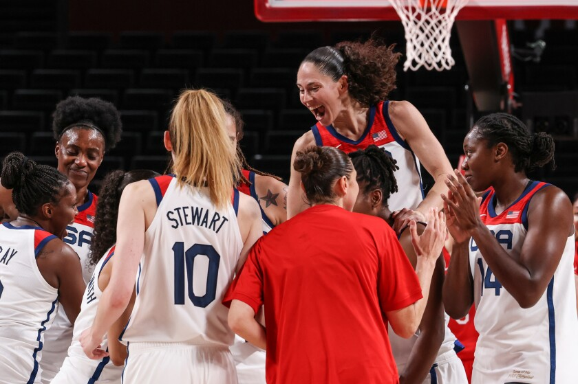 Players on the U.S. women's basketball team celebrate after beating Japan to win the gold medal.