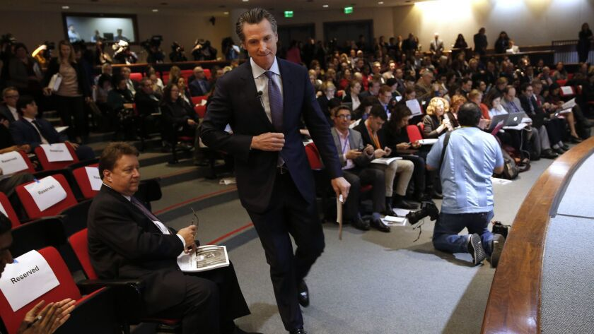 Gov. Gavin Newsom walks to the stage to present his first state budget during a Jan. 10 news conference in Sacramento.