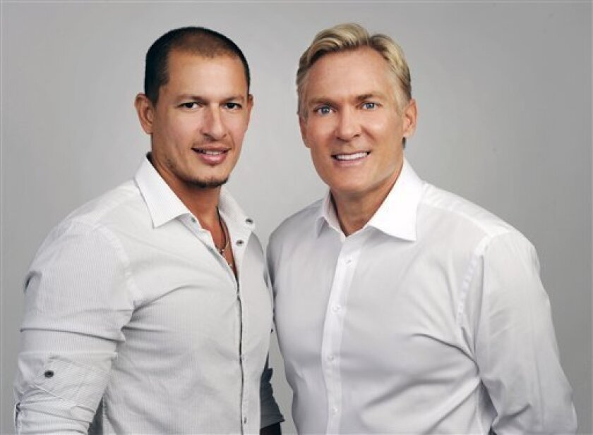 """This May 2012 photo released by ABC shows """"Good Morning America"""" weatherman Sam Champion, right, with Rubem Robierb in New York. ABC News says Champion and Robierb are engaged to be married later this year. Champion tweeted Friday, Oct. 5, that he's """"never been happier"""" to share a bit of personal news. Champion and Robierb met through mutual friends in Miami, where Robierb lives, according to ABC. Born in Brazil, Robierb is a fine-arts photographer who shows his work in Miami, Atlanta, Santa Monica and New York. (AP Photo/ABC, Ida Mae Astute)"""