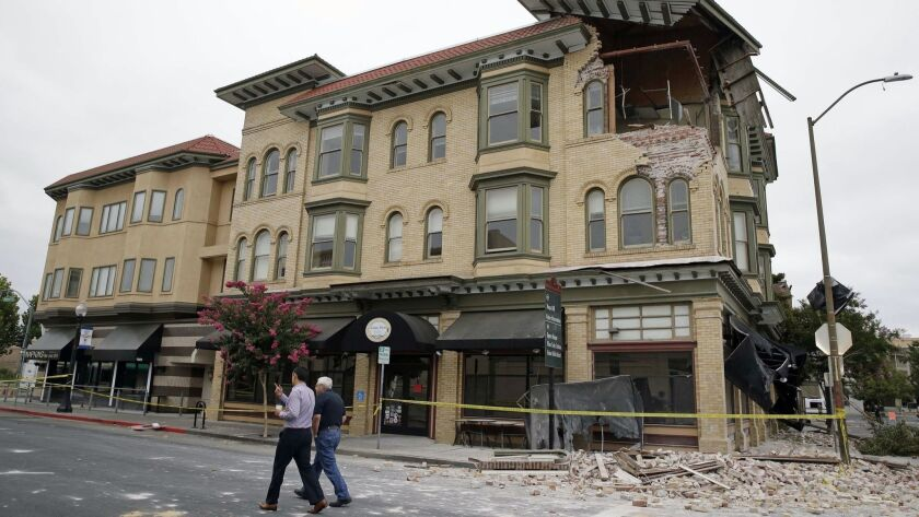 Two men walk past a quake-damaged building in Napa on Aug. 25, 2014. New research suggests the magnitude 6.0 earthquake that rocked California wine country may have been caused by an expansion of Earth's crust due to seasonally receding groundwater.