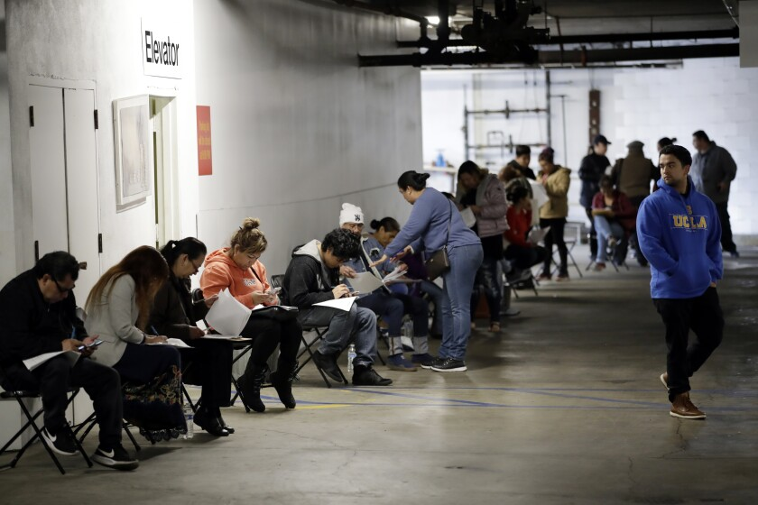 Workers wait to apply for unemployment benefits