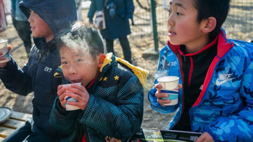 Boys have ginger tea prepared by the Real Boys Club after the run to warm themselves in Beijing, Chi
