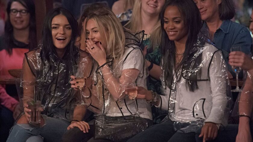 """Corinne Olympios, center, with Raven Gates, left, and this season's bachelorette, Rachel Lindsay, right, as they watch male contestants mud wrestle on """"The Bachelorette."""""""