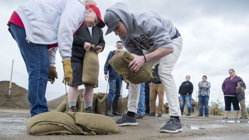 Ryan Revard, center, learns how to place sandbags to build a dike at the Kalispel Tribe headquarters in Usk, Wash., as part of a class Wednesday. Washington state Gov. Jay Inslee proclaimed a state of emergency Saturday for flooded counties in the region.