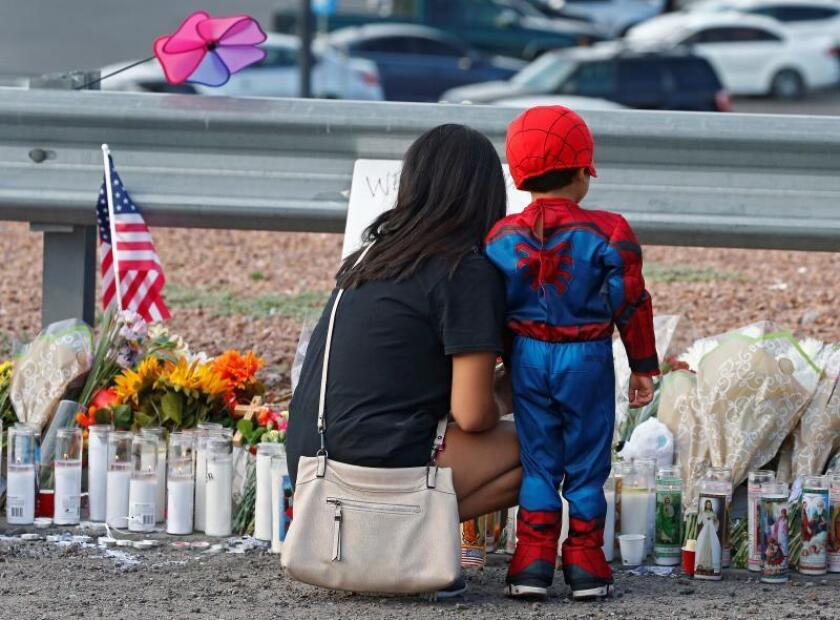 A woman and a young child pause while attending the make shift memorial along the street after the mass shooting that happened at a Walmart in El Paso, Texas, USA, 05 August 2019. EFE/EPA/Larry W. Smith