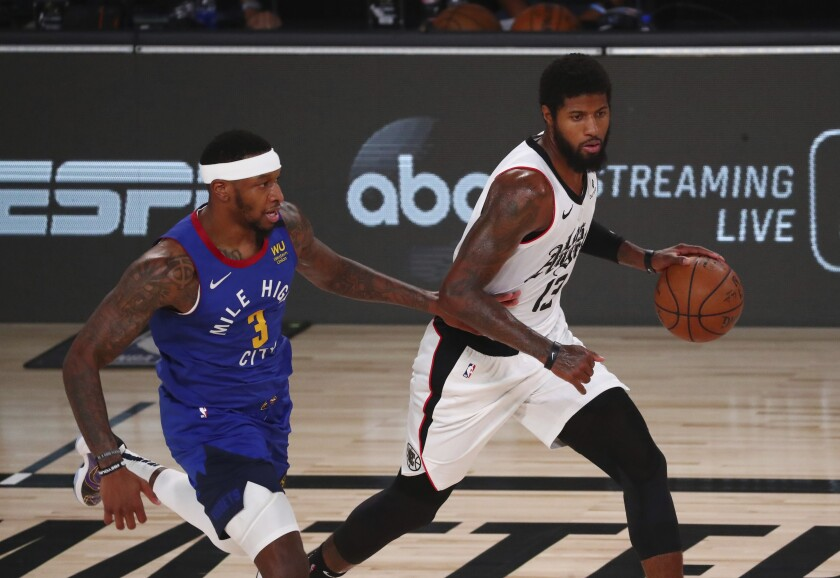 Clippers' guard Paul George controls the ball while defended by Denver Nuggets forward Torrey Craig.