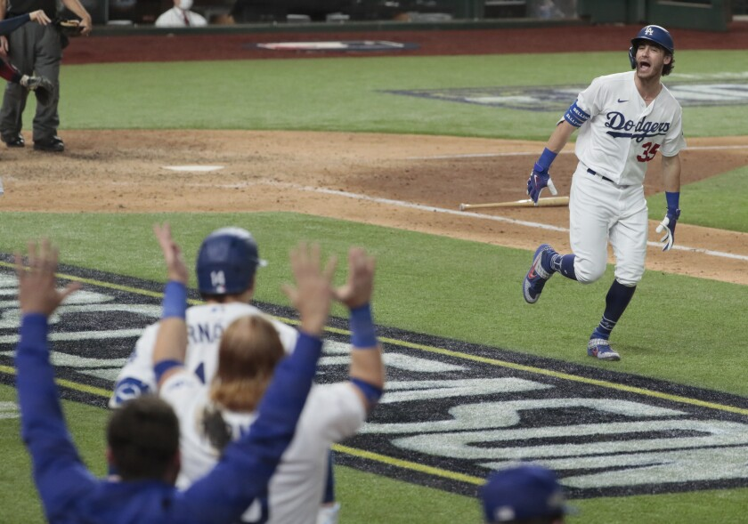 Cody Bellinger celebrates in front of the Dodgers' dugout during the playoffs.