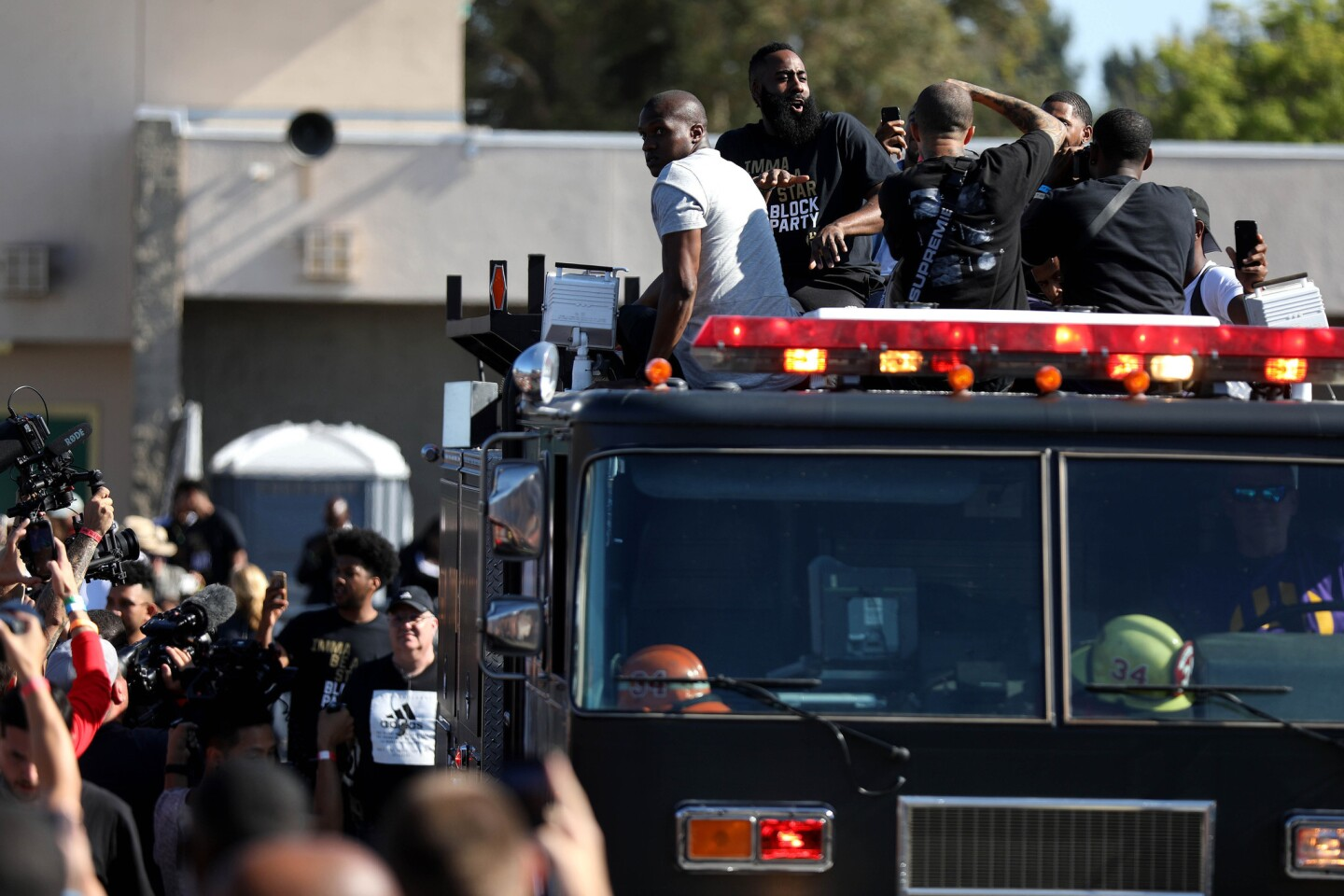 """NBA star James Harden arrives on a firetruck at the """"Imma be a star"""" block party on Sunday at Audobon Middle School, where he helped dedicate new basketball courts on the campus."""