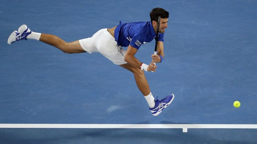 Novak Djokovic makes a backhand return to Rafael Nadal during the men's singles final at the Australian Open.