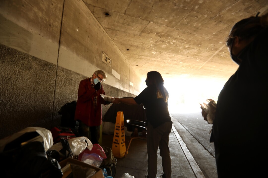 Outreach worker Judith Nuffio, center, gives Michael Cooper food while visiting his encampment under the 134 Freeway.