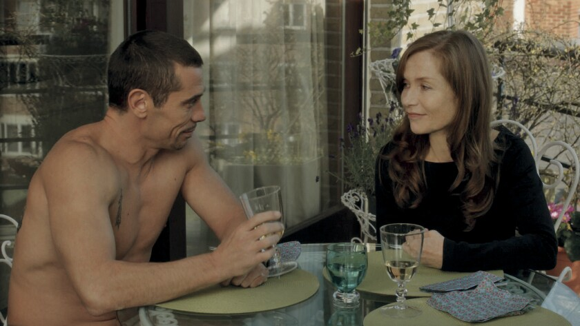 "Kool Shen, left, and Isabelle Huppert in the movie ""Abuse of Weakness."""
